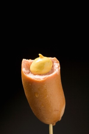 scalded sausage: Frankfurter, partly eaten, with mustard on cocktail stick LANG_EVOIMAGES