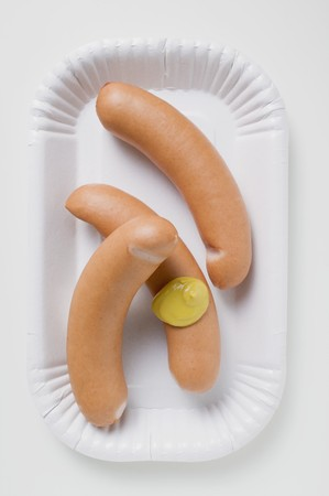 scalded sausage: Frankfurters with mustard on paper plate