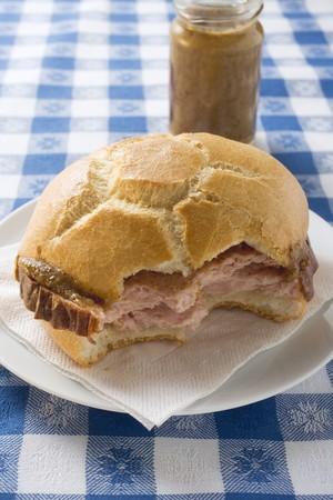 partly: Leberk�se in roll, partly eaten, on plate, jar of mustard behind