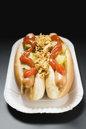 scalded sausage: Hot dogs with ketchup on paper plate