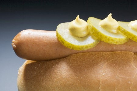 scalded sausage: Hot dog with gherkins and mustard (close-up)
