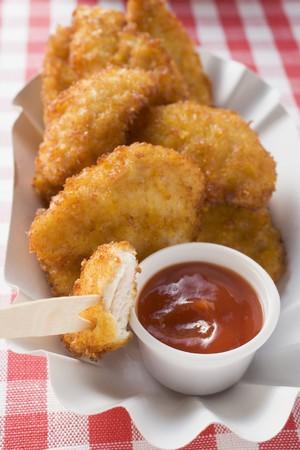 nuggets de poulet: Nuggets de poulet avec du ketchup dans un plat de papier LANG_EVOIMAGES