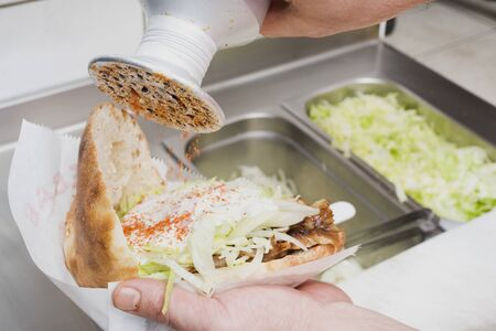 ner: Sprinkling seasoning on a d�ner kebab (opened)