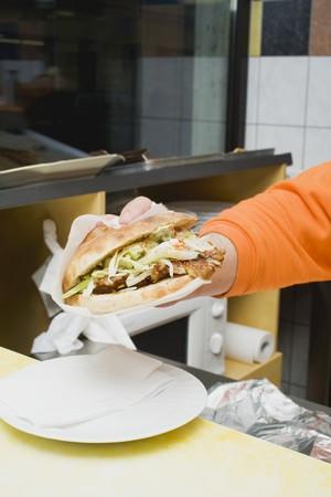 casse-cro�te: Mettre la main Adner kebab sur une plaque dans un snack-bar LANG_EVOIMAGES