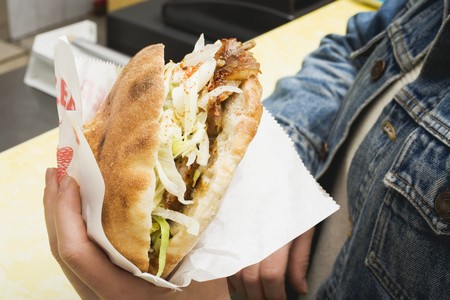ner: Hands holding a d�ner kebab in a snack bar LANG_EVOIMAGES
