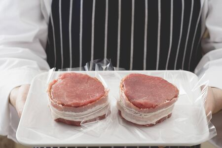 casings: Person holding two bacon-wrapped beef medallions on tray