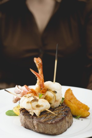 b n: Woman holding plate of Surf & Turf (beef steak with prawns) LANG_EVOIMAGES