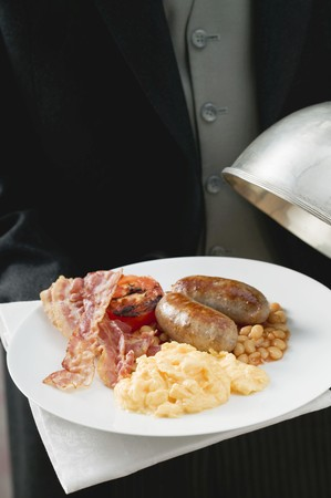 english breakfast: Butler serving English breakfast on plate with dome cover