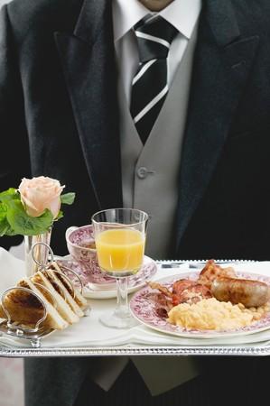 uk cuisine: Butler serving English breakfast on tray