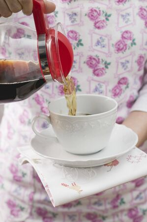 coffeepots: Woman pouring coffee into cup