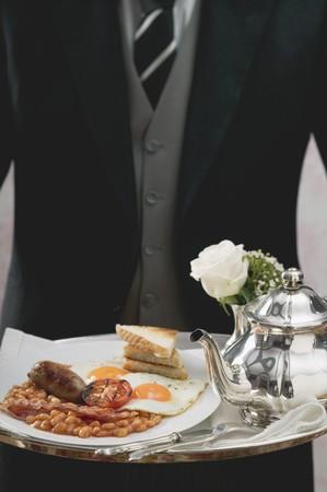 english breakfast: Butler serving English breakfast on tray