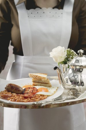 english breakfast: Chambermaid serving English breakfast on tray LANG_EVOIMAGES