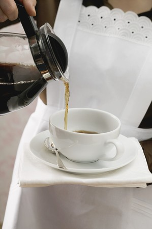 coffeepots: Chambermaid pouring coffee into cup LANG_EVOIMAGES