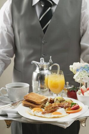 hashbrowns: Butler serving breakfast tray with bacon, eggs & toast
