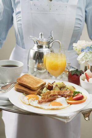 papas doradas: Camarera que sirve la bandeja del desayuno LANG_EVOIMAGES