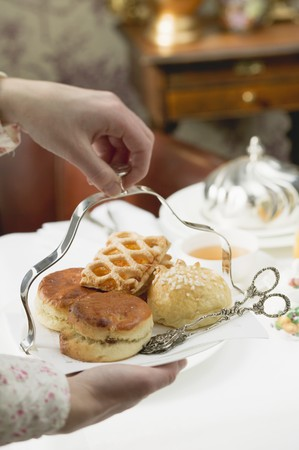 uk cuisine: Hands serving sweet pastries and scones to eat with tea
