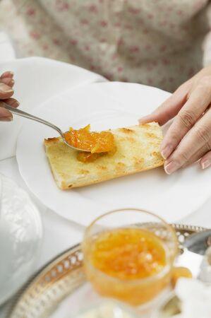 jams: Spreading orange marmalade on toast