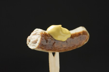 missing bite: Sausage with mustard on wooden fork