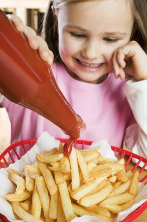 5 10 year old girl: Girl putting ketchup on chips