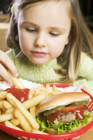 5 10 year old girl: Girl eating chips with ketchup and hamburger LANG_EVOIMAGES