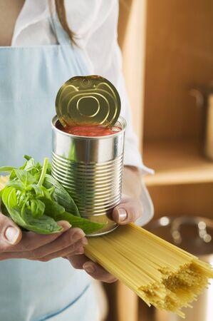 vegetable tin: Woman holding spaghetti, tin of tomatoes and basil