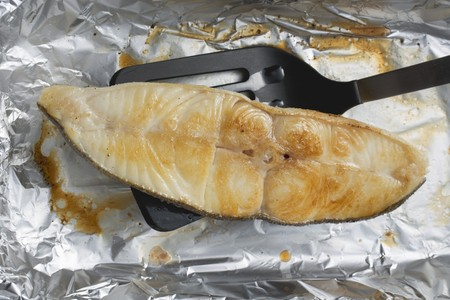 qs: Grilled cod steak on aluminium foil with spatula