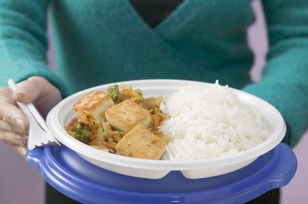well beings: Woman holding tofu, vegetables and rice on plastic plate