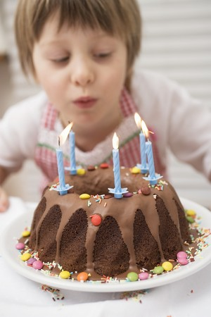 Small boy blowing out candles on birthday cake LANG_EVOIMAGES