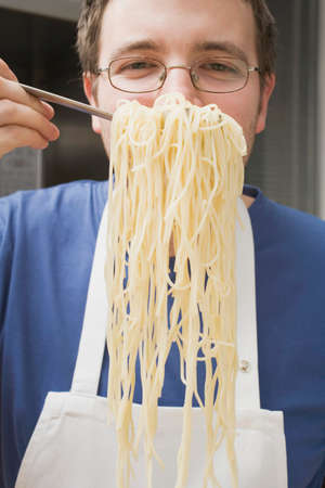 25 to 30 year olds: Chef holding up cooked spaghetti on spaghetti server LANG_EVOIMAGES