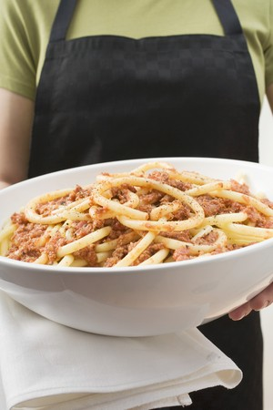 serve one person: Person holding bowl of macaroni with mince sauce