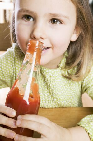 5 10 year old girl: Girl holding a bottle of ketchup
