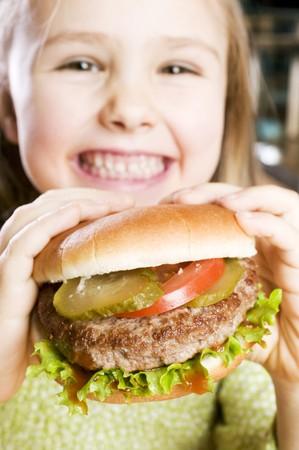 5 10 year old girl: Girl holding large hamburger