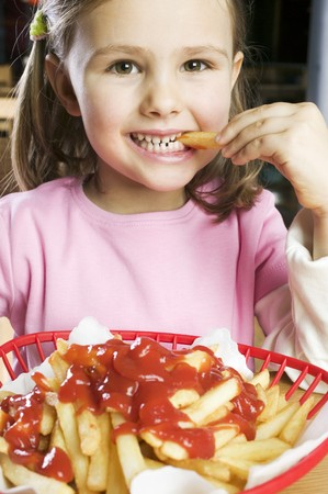 5 10 year old girl: Girl eating chips with ketchup LANG_EVOIMAGES