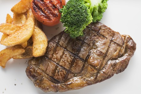 potato wedges: Grilled beef steak with vegetables and potato wedges