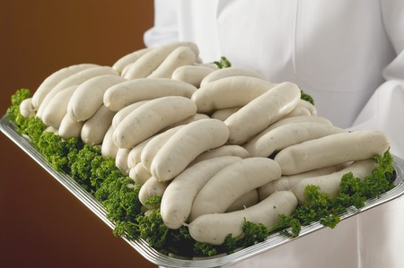 weisswurst: Person holding tray of Weisswurst (white sausages) LANG_EVOIMAGES