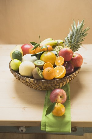 pip: An assortment of fresh fruit in a basket on a wooden table LANG_EVOIMAGES