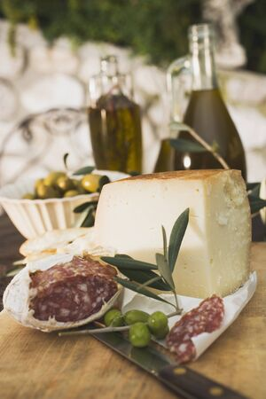 salame: Cheese, salami, olives and olive oil on table out of doors