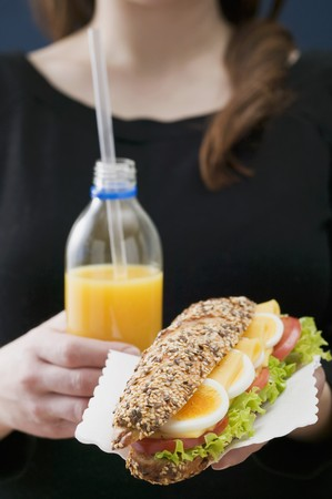well beings: Woman holding sandwich and bottle of orange juice