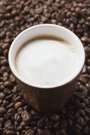 hot coffees: Cup of coffee with milk froth on coffee beans