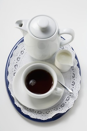 Black coffee in white cup, cream, coffee pot
