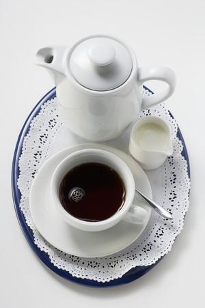 coffeepots: Black coffee in white cup, cream, coffee pot