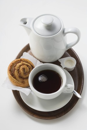 coffeepots: Cup of coffee, cinnamon bun, cream and coffee pot on tray