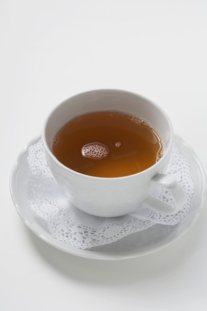 doiley: Tea in white cup and saucer with doily