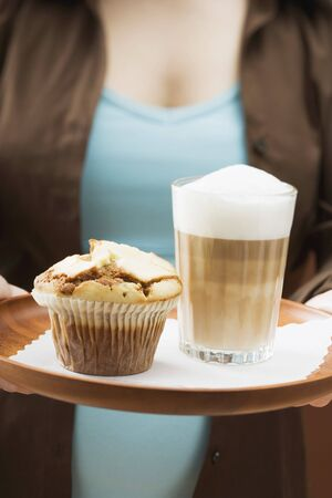 hot coffees: Woman holding tray with latte macchiato and muffin