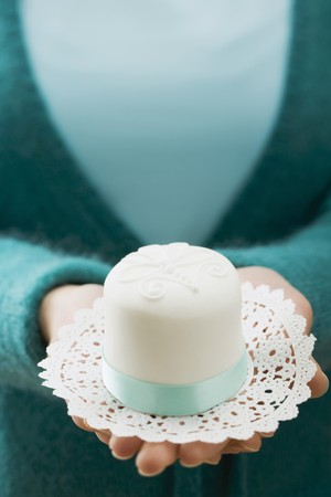 doiley: Woman holding a small white cake on a doily