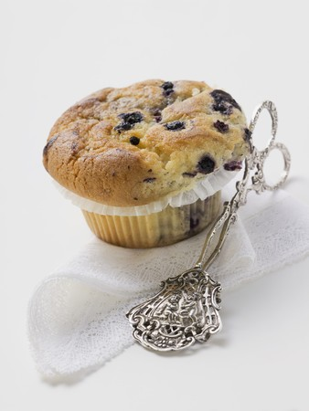 blueberry muffin: Blueberry muffin in paper case, cake tongs beside it