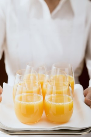hold ups: Chambermaid serving several glasses of orange juice on tray LANG_EVOIMAGES