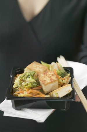 beancurd: Fried tofu with vegetables, woman in background (Japan)