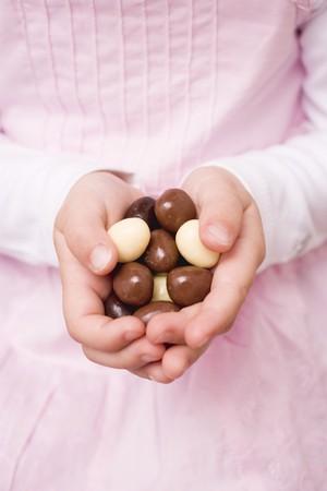 oeufs en chocolat: Les mains de l'enfant tenant des ?ufs en chocolat