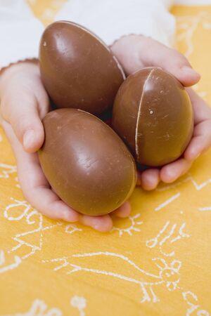 oeufs en chocolat: Les mains de l'enfant tenue de trois oeufs en chocolat LANG_EVOIMAGES